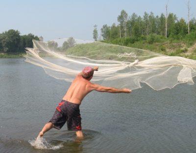 Рыболов делает заброс кастинговой сети